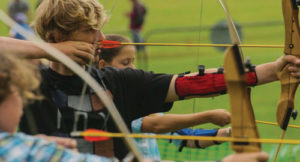 summer school students practising archery